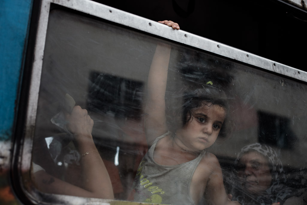 Gevgelia, Macedonia - August 8, 2015: A child refugee is seen observing from the inside of the train headed towards Serbia, as train is about to depart from Gevgelia train station.