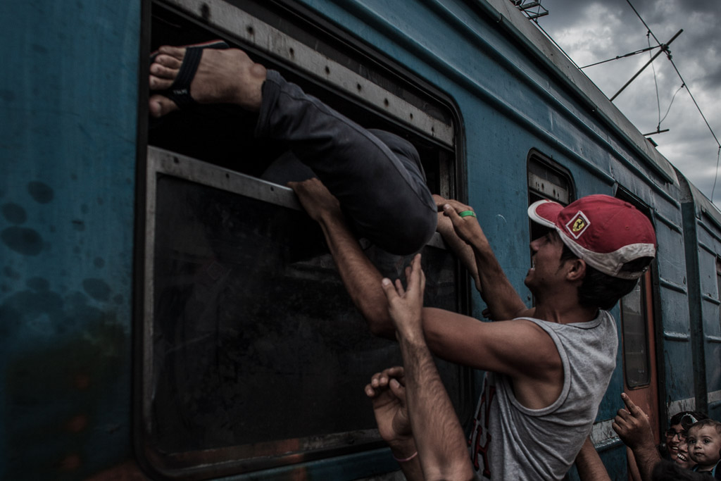 Gevgelia, Macedonia - August 8, 2015: Refugees try to climb into a carriage of the train through open windows in order to secure them some space before carriage is full. Their colleagues and family members pass them their personal belongings as they follow their attempts to enter the train through the windows.
