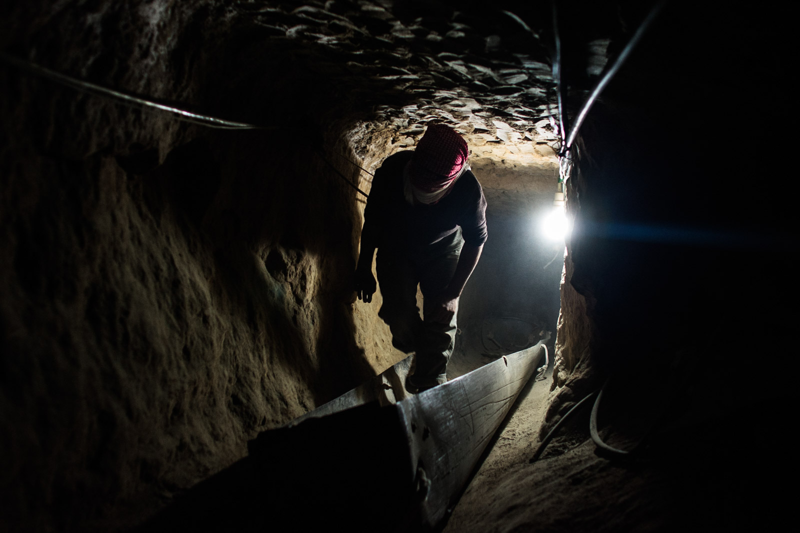 Rafah, Gaza - January 2, 2011: An unidentified smuggler walks through an underground tunnel below border of Egypt and Gaza. Tunnels serve as an illegal passage to Egypt for numerous Palestinians which try to flee Gaza.