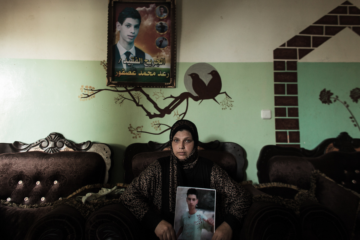 Khan Younis, Gaza - September 27, 2014: Mother of Rae'ed Asfour holds a portrait of his drowned son. She is one of the numerous mothers awaiting for any official information of her child's death. Rae'ed was on a ship that sank in the Mediterranean on September 6. He was included in the rehabilitation program after sustaining injuries in Israeli military operation on Gaza in 2009. At age of 16 he fled Gaza with intention to live with his father in Norway. Rae'ed's commemoration photo is seen hanging on the wall.