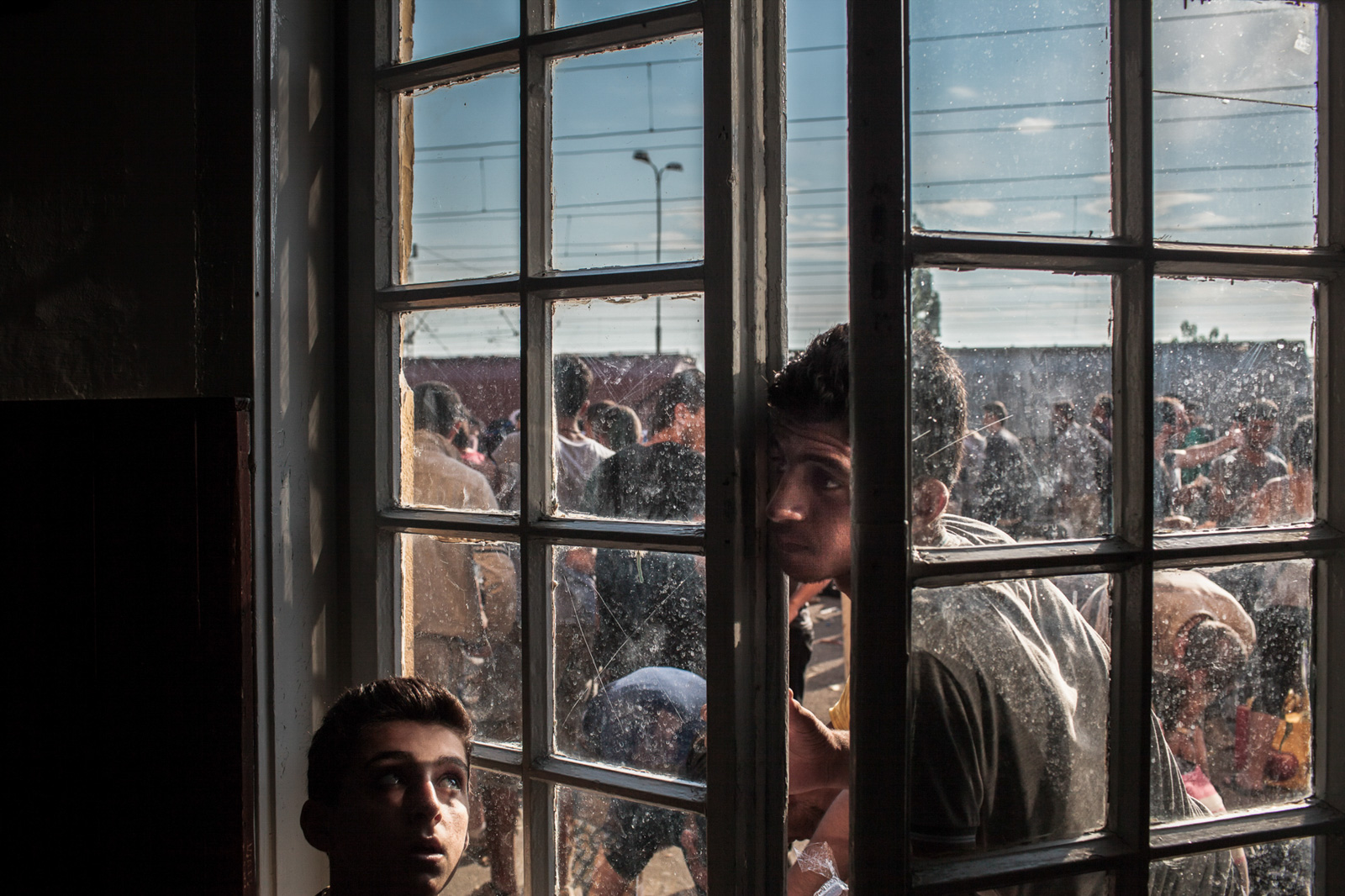 GEVGELIA,MACEDONIA - AUGUST 8, 2015: A young refugee is looking through a window of train station in Gevgelia, Macedonia, while waiting to board the train headed towards Serbia. Each day about 1500 refugees cross from Greece to Macedonian town of Gevgelia with intention to reach any of European Union countries and to receive status of asylum seekers there.