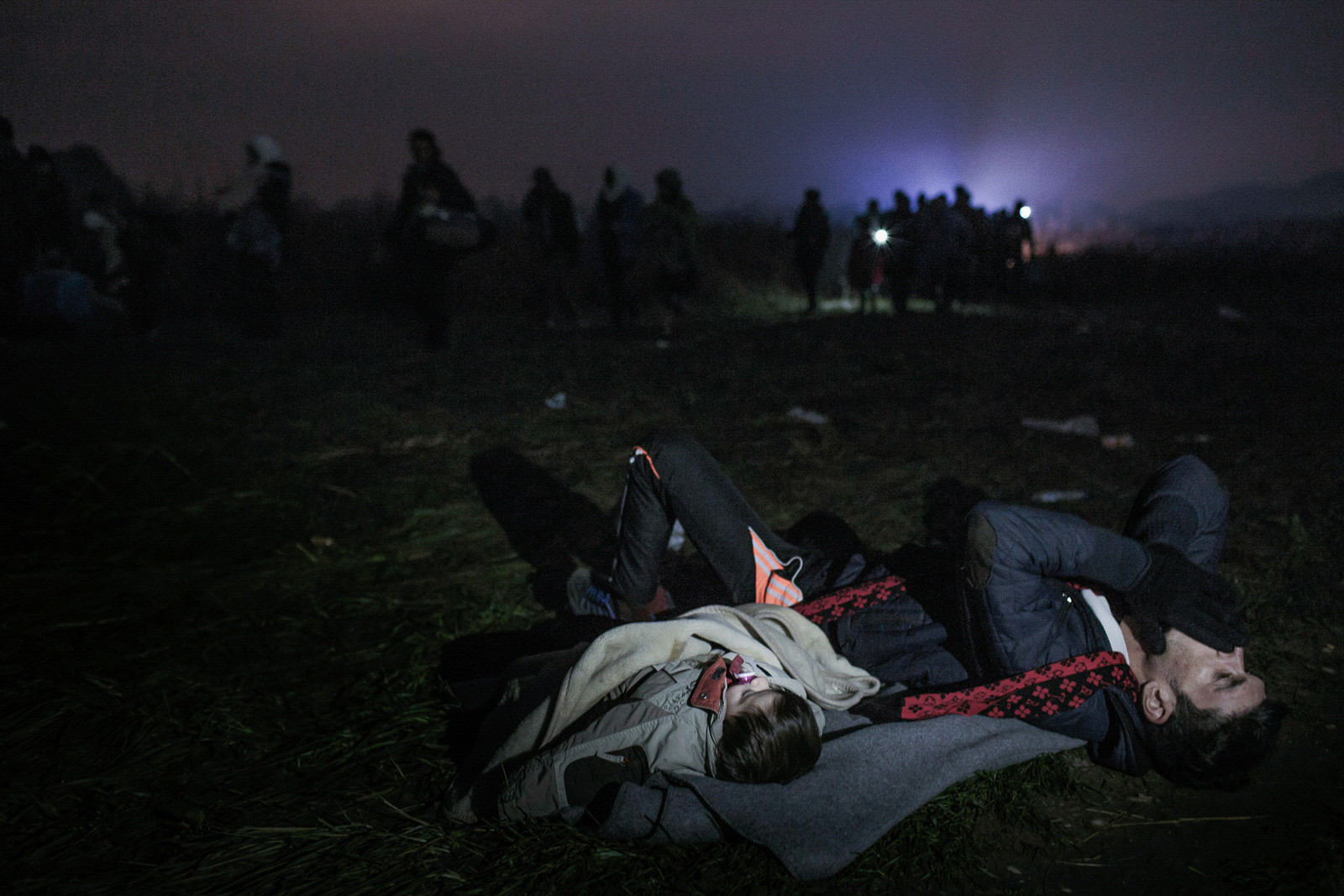 Brežice, Slovenia - October 26, 2015: Refugees walk about eight kilometers towards the refugee registration center in Brezice during the night. Some tired ones stop to rest in open fields. Khalil, a Kurd from Syria has lost his family somewhere inside that colossal group of people. In absolute desperation, he had no choice but to lay down the field with his baby, shouting the name of his loved ones as he awaits for them.
