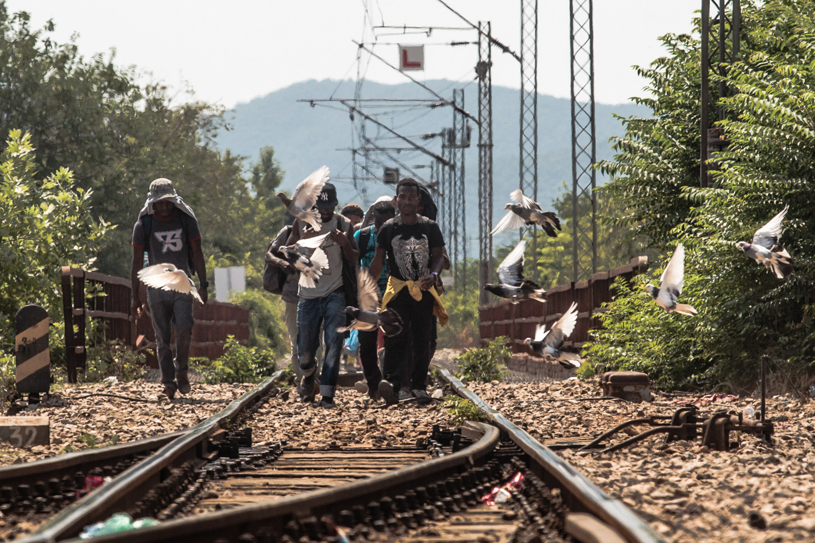 Gevgelia, Macedonia - August 8, 2015: A group of asylum seekers who crossed from Greece to Macedonia follow the lead of railroad track heading towards Gevgelia train station, from where they proceed towards Serbia and the countries of the European Union.