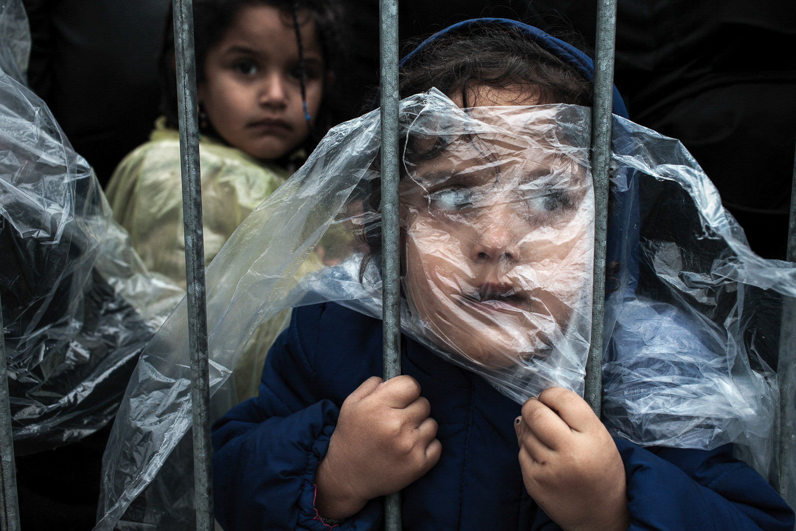 Preševo, Serbia - October 7, 2015: A child refugee is covered with raincoat while she waits in line to get registered in Preševo refugee registration camp. Most of the refugees who crossed Serbia try to continue their route towards Hungary, Croatia, Slovenia and other countries of the European Union.