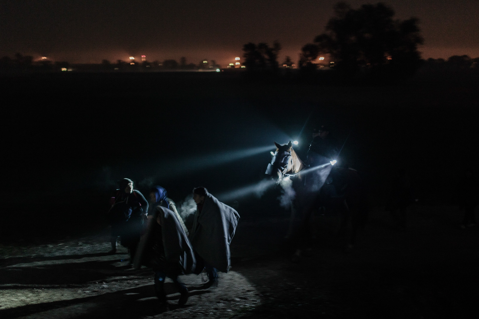 Brežice, Slovenia - October 26, 2015: Refugees are marching towards refugee registration center in Brezice during the night. The nights are getting colder, with air temperature being as low as five degrees Celsius. The Slovenian police provides an escort for the refugees on their eight kilometer march from Rigonce, where they enter Slovenia.