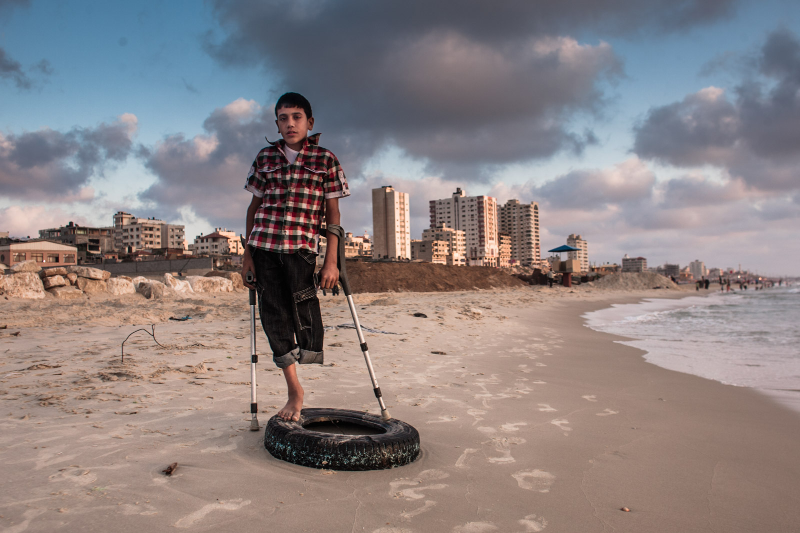 Gaza City, Gaza - June 7, 2011: Fadi Al-Arir poses for a portrait on a beach in Gaza City, Gaza Strip. Fadi injured his leg playing football in his home in December 2008. Due to inadequate medical treatment and rehabilitation, Fadi's broken leg had to be amputated due to gangrene infection. During the Israeli military operation dubbed Cast Lead in December 2008 and January 2009, hospitals in Gaza were overcrowded causing insufficient availability of medical care. In 2010 Fadi was part of the Slovenian University Rehabilitation Center Soča program for juvenile victims of war where he was taught to use prosthetic legs, which he outgrew after a year, rendering it useless.