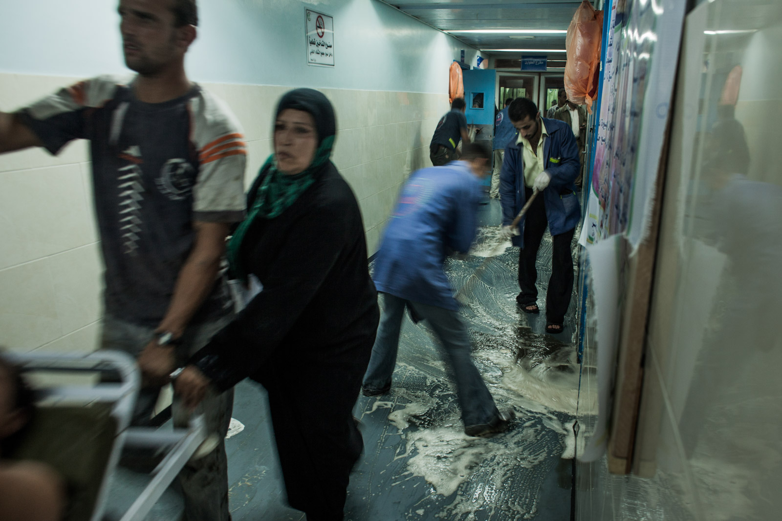 Gaza City, Gaza - November 10, 2012: Janitors clean blood off the floor in the hallway of Shifa hospital in Gaza, while numerous patients are transferred from the emergency unit to the surgery rooms while air strikes in Gaza strip continue, increasing the tensions even before the Israeli military operation Pillars of Cloud officially began.