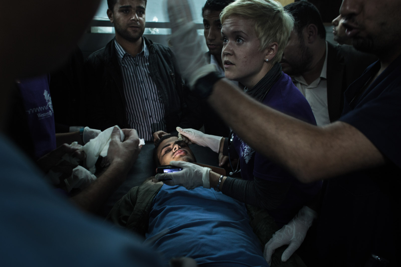Gaza City, Gaza - November 10, 2012: International medical reservists give orders to medical personnel in the emergency unit of Shifa hospital in Gaza, after examining the pupils of the injured with the aid of a cell phone light.